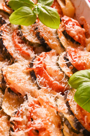 Eggplant with parmesan. Traditional italian food. Baked eggplant, tomatoes with sauce, parmesan and basil. Rustic food for a healthy diet. Vegetables for lunch. Place for your text.postcard with food.