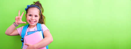 Schoolgirl with a backpack and books with colored covers on a green background. The little girl is happy and happy, ready to go to school. Great place for text. Bann, long format