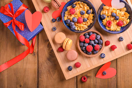 Muesli with berries and sweet pastries for a romantic breakfast. A surprise for dad on fathers day or for mom. High quality photo. Copy space. Above