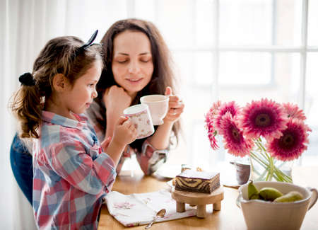 Mom and daughter have breakfast in a bright room near the window. The concept of relations of children and parents. Flowers on the table, sweet cake and tea. Copy space.