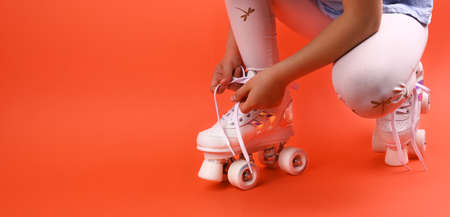 Little child with roller skates, a blue helmet on a red background, tying shoelaces. A girl of 7 years old poses and prepares for active leisure on retro ice skates. Copy space Zdjęcie Seryjne