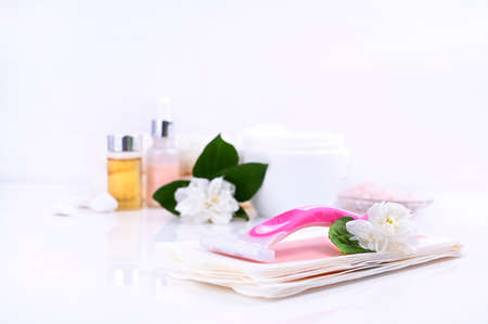 a set of different means for epilation on a colored background. Removal of unwanted hair. Body care products, creams, emulsion,towel, jasmine flowers, wax strips, razor. Minimalism, top view. flatlay.