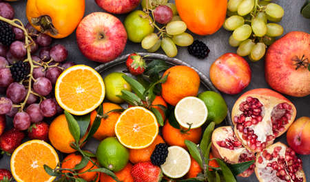 Assorted fruits. Different fruits on a gray background, the whole surface is covered with citrus fruits, pomegranates, apples, grapes, strawberries. Top view Stock fotó