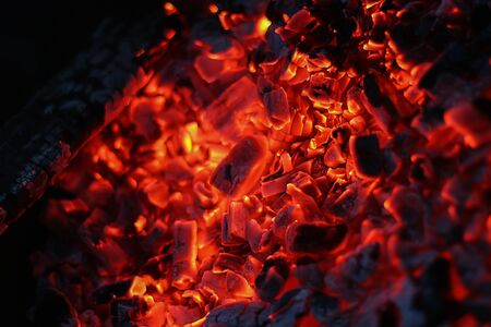 Smoldered logs burned in vivid fire close up. Atmospheric background with orange flame of campfire. Unimaginable detailed image of bonfire from inside with copy space. Smoke and glowing embers