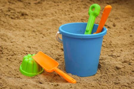 Children's beach sand toys. Kids concept. Plastic children's toys. Blue bucket, colorful molds. Kids toys, on sand beach in summer day. Standard-Bild