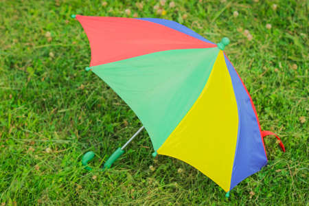 A colorful children's Umbrella on the green Lawn. The concept of a happy childhood. International Children`s Day Foto de archivo