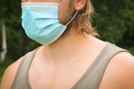 A beard Man in a blue medical mask. The concept of preventing the spread of coronavirus infection COVID-19. Stock fotó