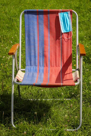 Blue face Mask on the handle of the Deckchair. Concept of social distance. Coronavirus Quarantine stop. The concept of preventing the spread of coronavirus infection COVID-19.