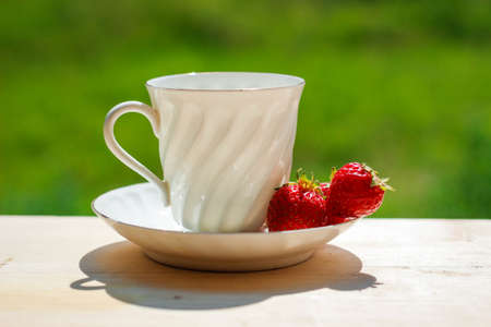 Elegant white porcelain Cup with a Saucer and Strawberries on a wooden Terrace against the background of Nature. Russian Imperial Porcelain. Morning concept. Beverage, breakfast.