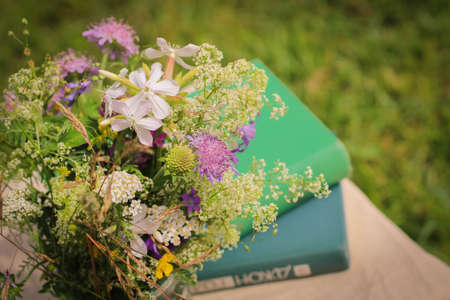 A beautiful bouquet of wildflowers and the books on a soft green summer background of summer garden.