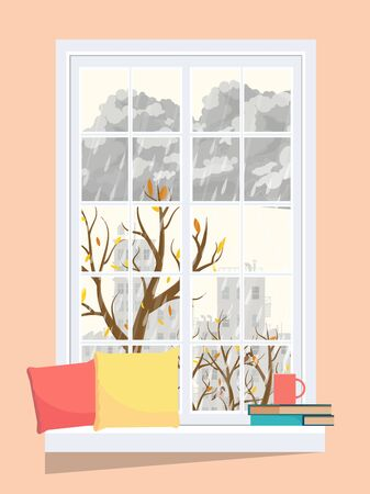 A cozy window with an autumn landscape with pillows, books and a cup on the windowsill.
