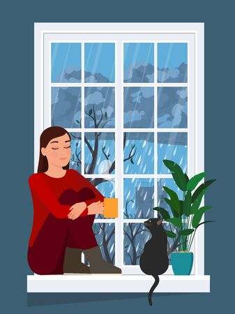 Girl drinks a hot drink while sitting on a windowsill with a cat.
