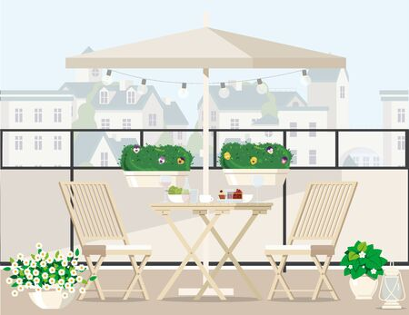 White garden furniture surrounded by plants on the balcony under an umbrella overlooking the city.