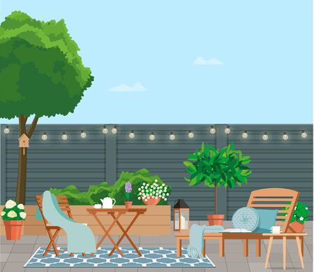Back patio with garden furniture on a background of green plants.