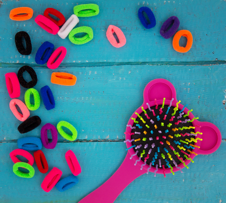 Pink baby hairbrush and multicolored rubber bands for hair on a blue wooden background.