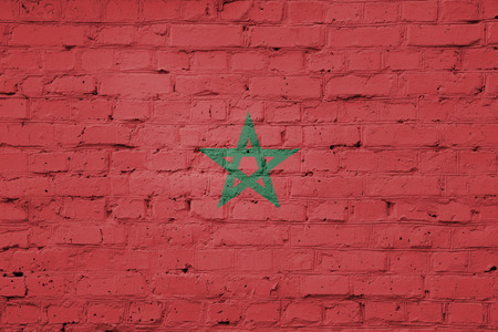 Texture of a flag of Morocco on a pink brick wall.