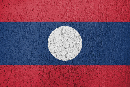 Texture of Laos Peoples Republic of Korea flag on the wall of relief plaster.