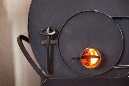 Wood burning iron stove with burning planks.
