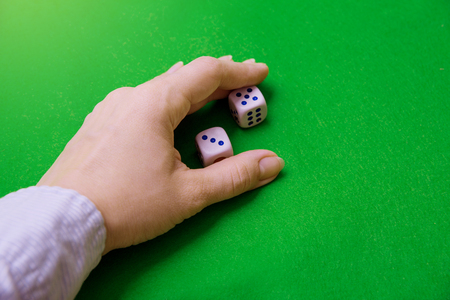 Hand rakes dices on green cloth. Dropped three and five.