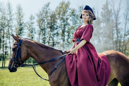 Beautiful girl in black hat with a cocked hat riding a brown horse. Looks at the camera. Фото со стока