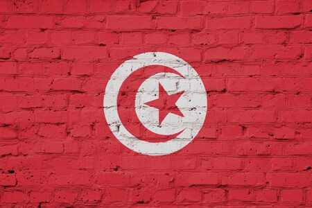 Texture of a flag of Tunisia on a brick wall.