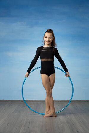 Girl gymnast swimsuit holding a hoop behind. She stands on a blue background. Imagens