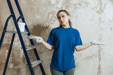 A young woman in work clothes tiredly wearily in perplexity throws up her hands while preparing the wall for painting. Standard-Bild - 139787517