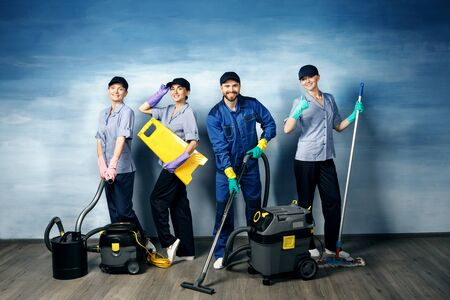 Three attractive girls and one young man with a beard in a working uniform for cleaning are holding items for cleaning on a blue background. Standard-Bild - 140326725