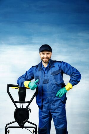 A young attractive man with a beard in a working uniform is standing next to a floor cleaning machine on a blue background.