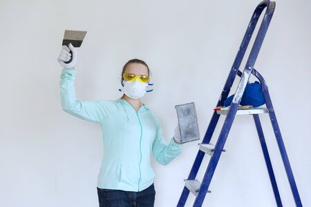 A young woman in work clothes and a respirator prepares a wall for painting, holding a grater for polishing the walls and a spatula in front of a white wall and ladder.