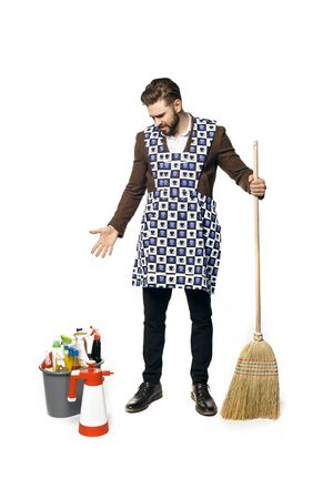 Young attractive guy in a businessman suit and home apron for cleaning, looks at the bucket in surprise and holds a broom in his hands isolated on white bacground Standard-Bild - 140326729