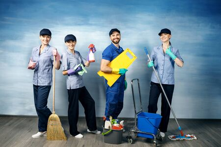 Three attractive girls and one young man with a beard in a working uniform for cleaning are holding items for cleaning on a blue background. Standard-Bild - 140326731
