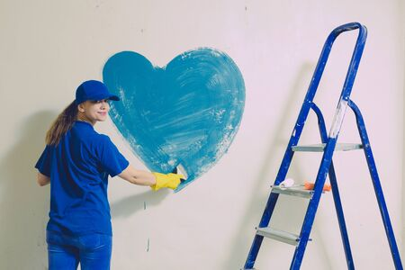 A young woman in a blue T-shirt in yellow rubber gloves and cap is painting a wall in an apartment, there is a staircase nearby. Standard-Bild - 139837531