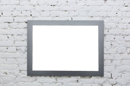 Marco vacío de una pintura sobre una pared de ladrillo blanco. Foto de archivo
