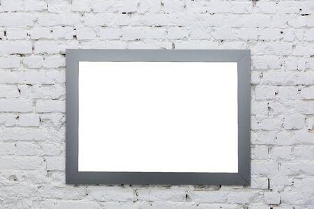 Pusta rama z obrazu na białej ścianie z cegły. Zdjęcie Seryjne