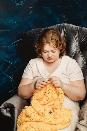 A beautiful plump redhead young woman with freckles sits in an armchair and knits a sweater. Standard-Bild - 139814139