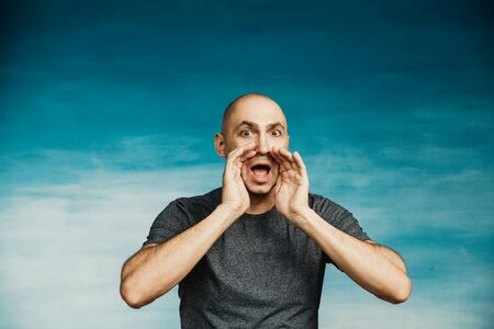 A bald man in a gray T-shirt screams, opening his eyes wide and raising his hands to his mouth like a shout. On a blue Standard-Bild - 139814157