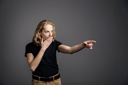A young guy with long blonde hair pokes his index finger to the side in surprise. A young man is showing something on a gray background. Archivio Fotografico