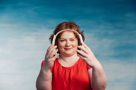 Young attractive plump woman with red hair holds headphones forward Standard-Bild - 139814262