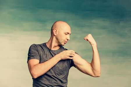 Young bald man in a gray T-shirt and jeans boasts of his biceps on a blue wall Standard-Bild - 139814283