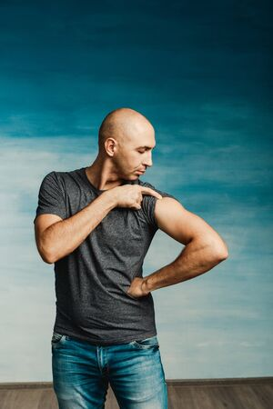 Young bald man in a gray T-shirt and jeans boasts of his biceps on a blue wall Standard-Bild - 139814286