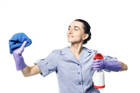 A beautiful young woman in the uniform of a maid holds a rag and spray for washing windows and looks at them with smile. Isolated Standard-Bild - 139814297