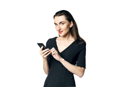 Business woman (fatal woman) in a black dress with red lipstick looks at her phone, isolated on a white