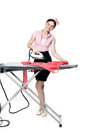 A beautiful girl dressed in pin-up style is ironing clothes isolated Standard-Bild - 139814380