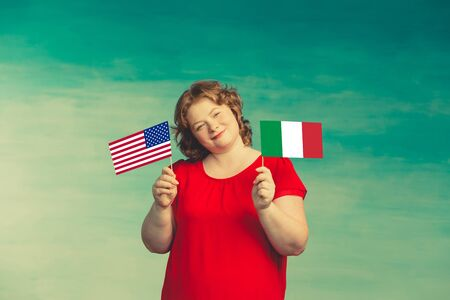 Red-haired plump woman holding Italian and American flags in front of her Standard-Bild - 139814421