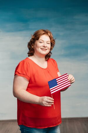 A plump young woman holding american flag and smiling Standard-Bild - 139814423