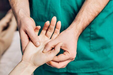 Masaż nadgarstka. Masażysta mężczyzna kładzie nacisk na wrażliwy punkt na dłoni.