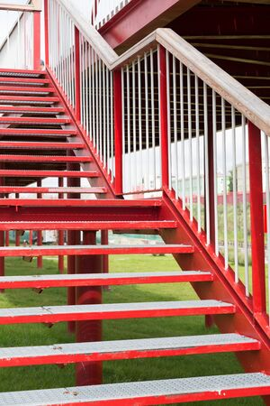 Red steps of a metal staircase outside. Standard-Bild - 139707682