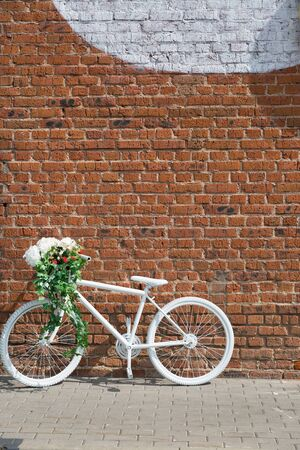 White decorative old bike with a basket of flowers against a brick wall. Standard-Bild - 139709582