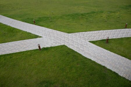 Pavement made of tiles in the form of a cross surrounded by a lawn of green grass. Standard-Bild - 139711132